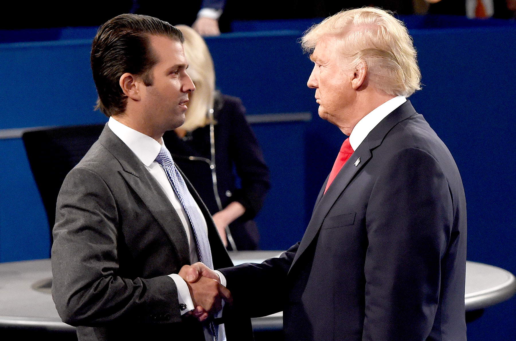 Donald Trump Jr. greets his father, Donald Trump, during the town hall debate at Washington University in St. Louis, Missouri, on October 9, 2016.