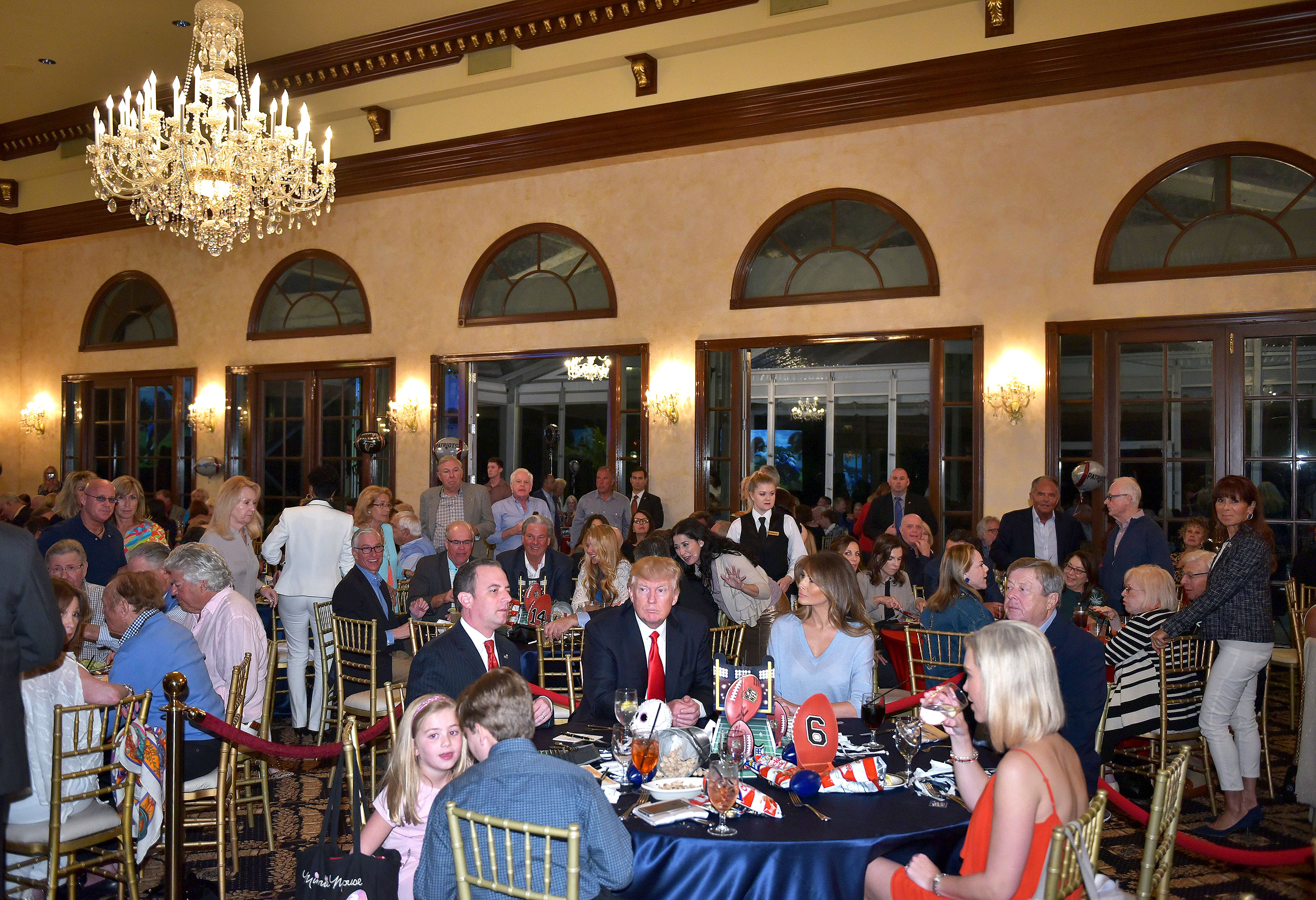 Donald Trump watches the Super Bowl with First Lady Melania Trump (R) and White House Chief of Staff Reince Priebus (L) at Trump International Golf Club Palm Beach in West Palm Beach, Florida on February 5, 2017.