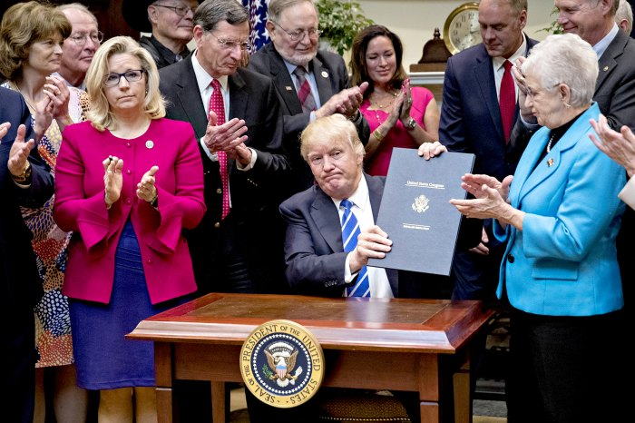 Donald Trump holds up H.J. Res. 58, which overturns a rule requiring states to report specific information on teacher preparation programs, such as student learning outcomes, and rate their effectiveness, after signing the bill during a ceremony in the Roosevelt Room of the White House in Washington, D.C., U.S., on Monday, March 27, 2017.