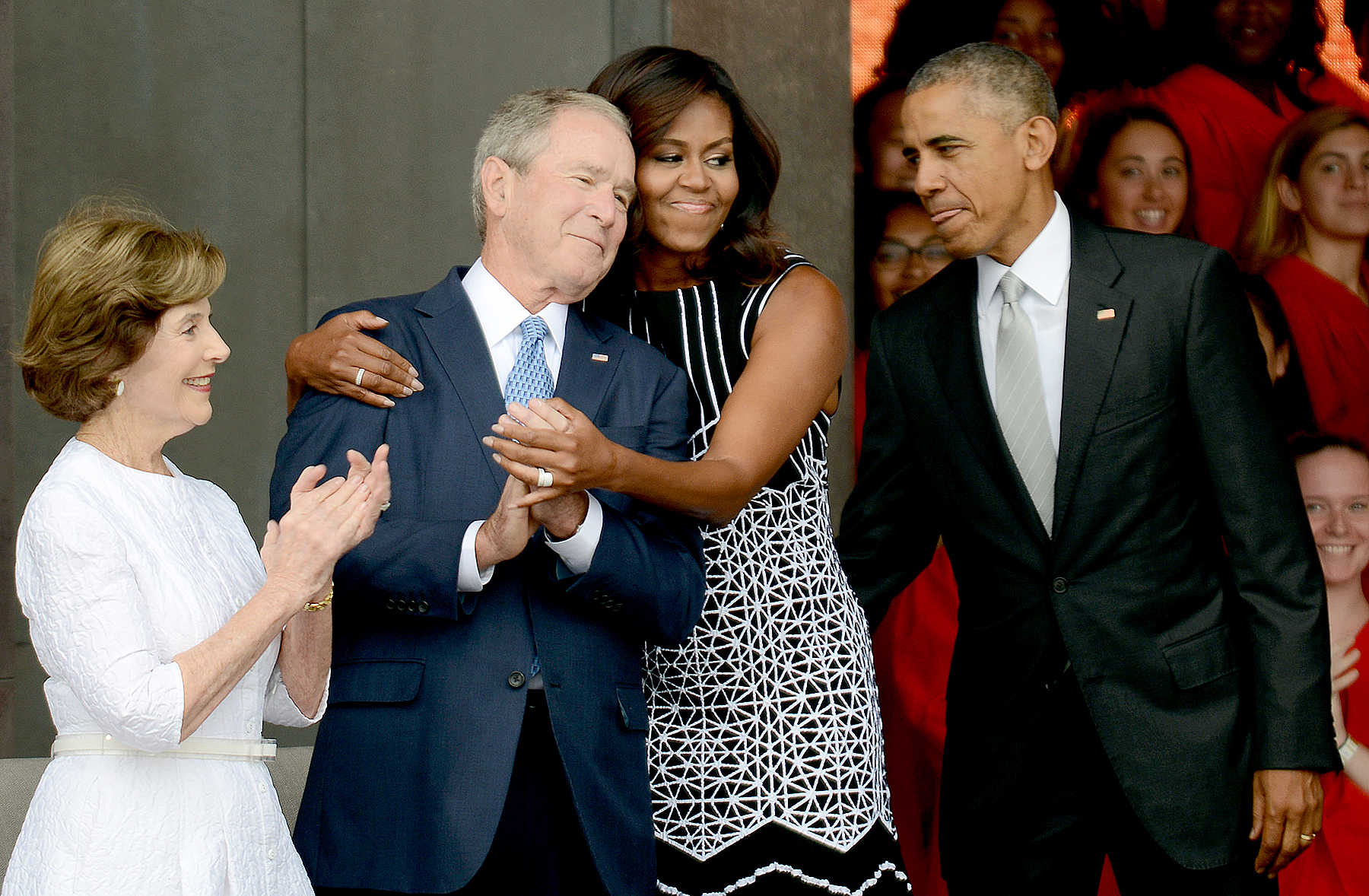 Barack Obama watches Michelle Obama embracing former president George Bush, accompanied by his wife, former first lady Laura Bush, while participating in the dedication of the National Museum of African American History and Culture September 24, 2016 in Washington, DC.