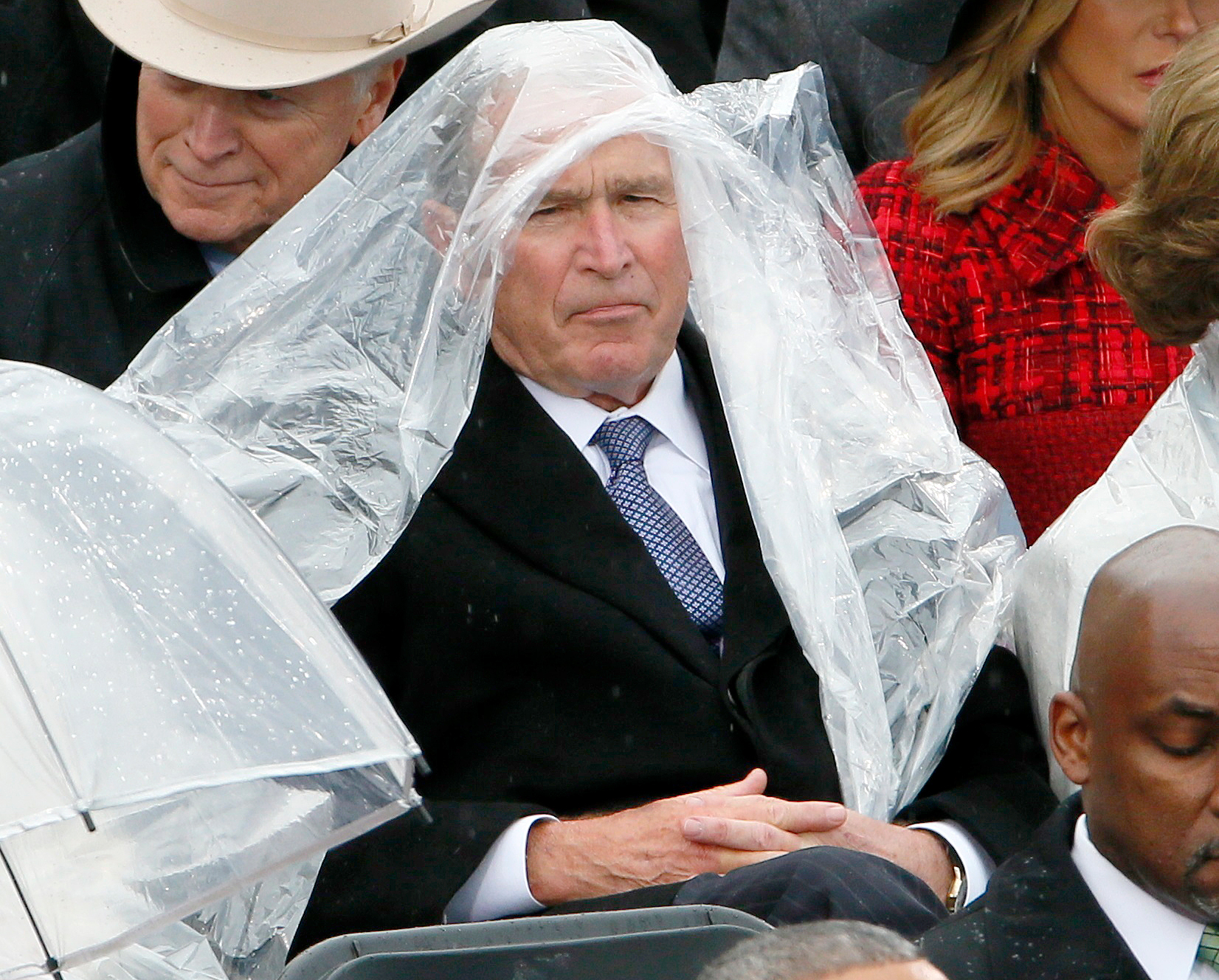 Former President George W. Bush keeps covered under the rain during the inauguration ceremonies swearing in Donald Trump as the 45th president of the United States on the West front of the U.S. Capitol in Washington, U.S., January 20, 2017.