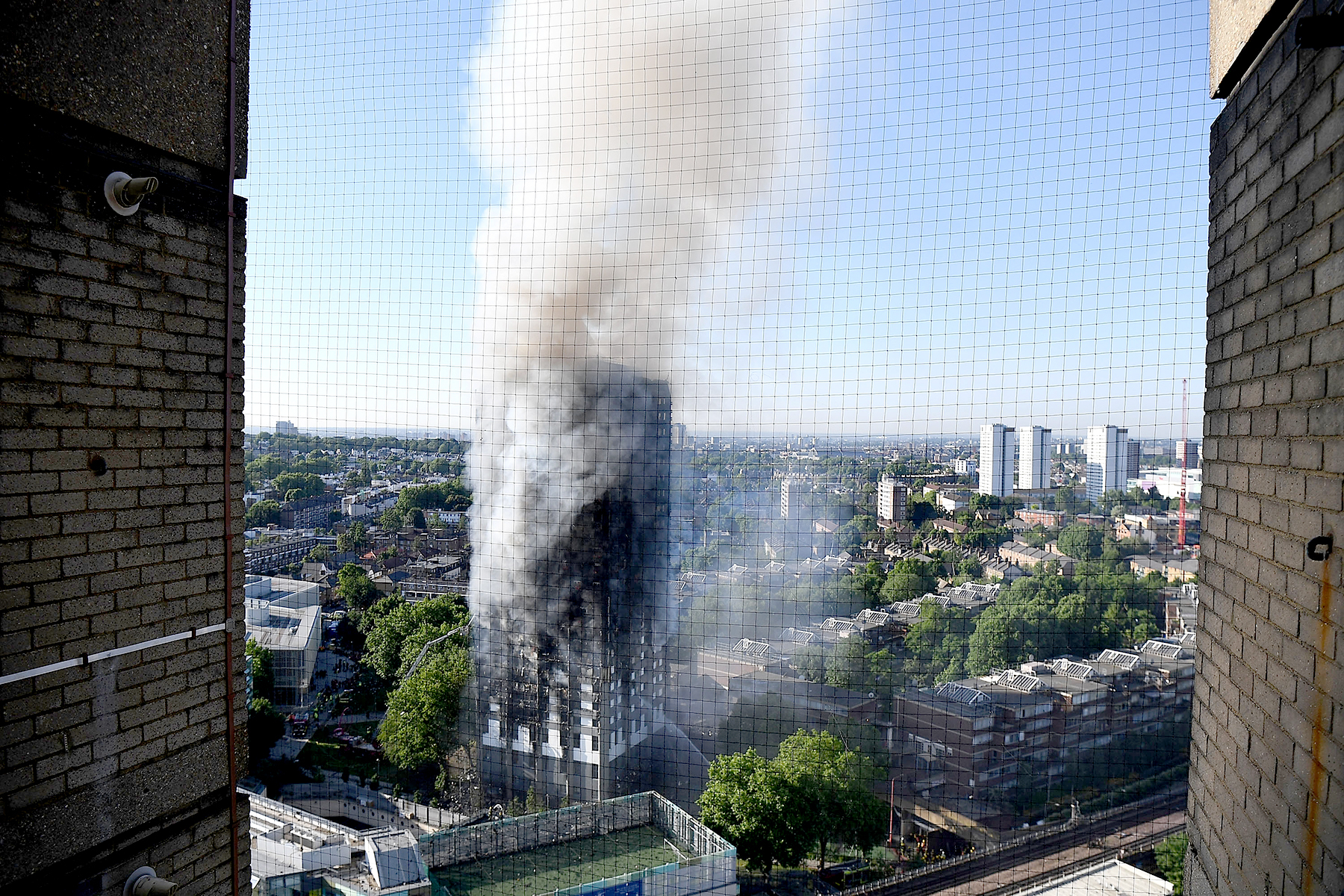 Smoke rises from the building after a huge fire engulfed the 24 storey residential Grenfell Tower block in Latimer Road, West London in the early hours of this morning on June 14, 2017 in London, England.