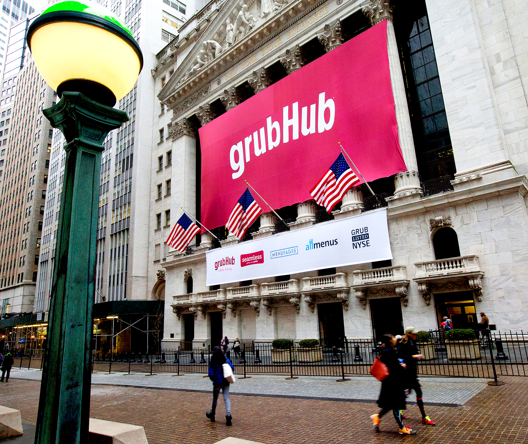 Pedestrians walk past a GrubHub Inc. banner on the exterior of the New York Stock Exchange in New York.