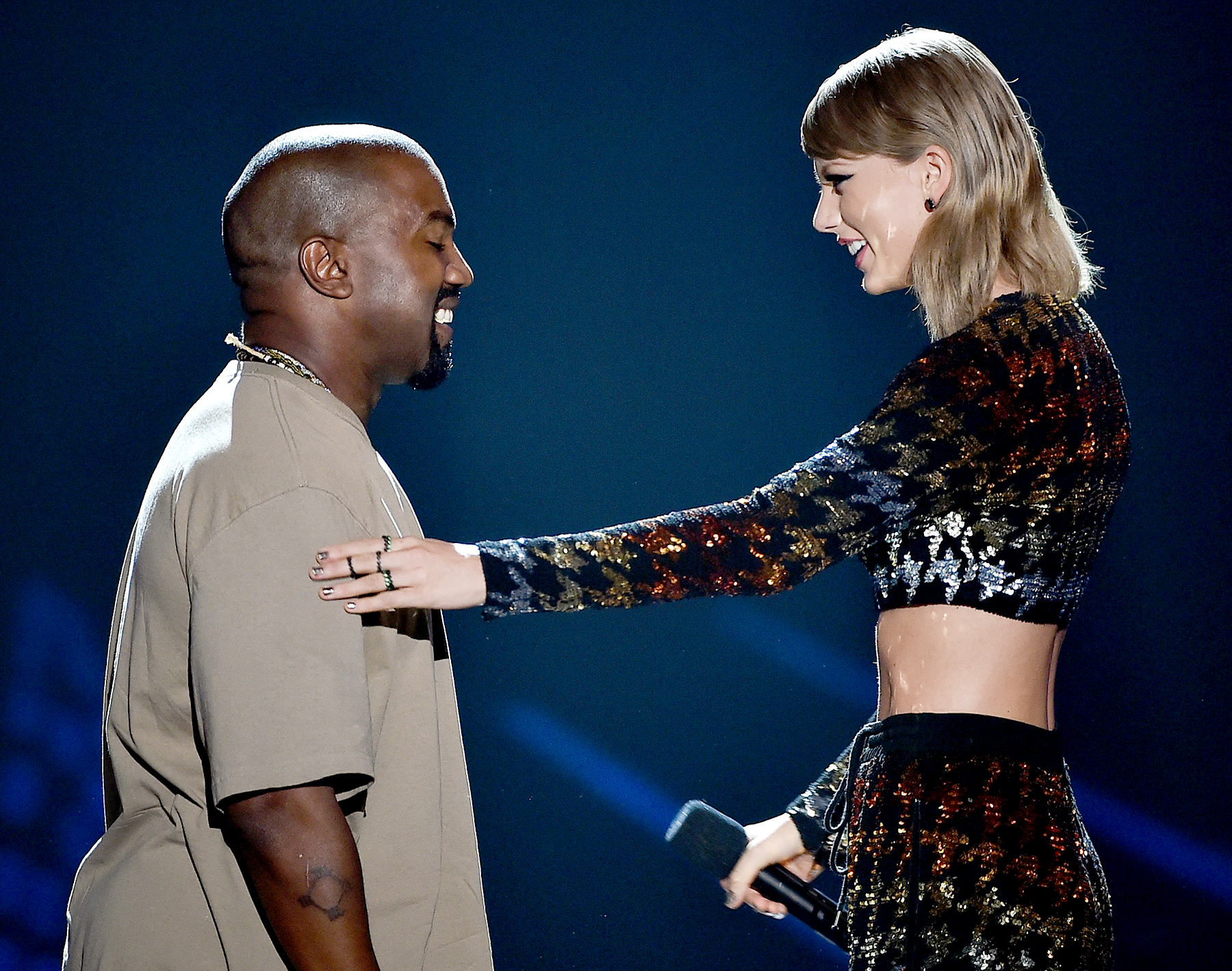 Recording artist Kanye West accepts the Video Vanguard Award from Taylor Swift onstage during the 2015 MTV Video Music Awards.