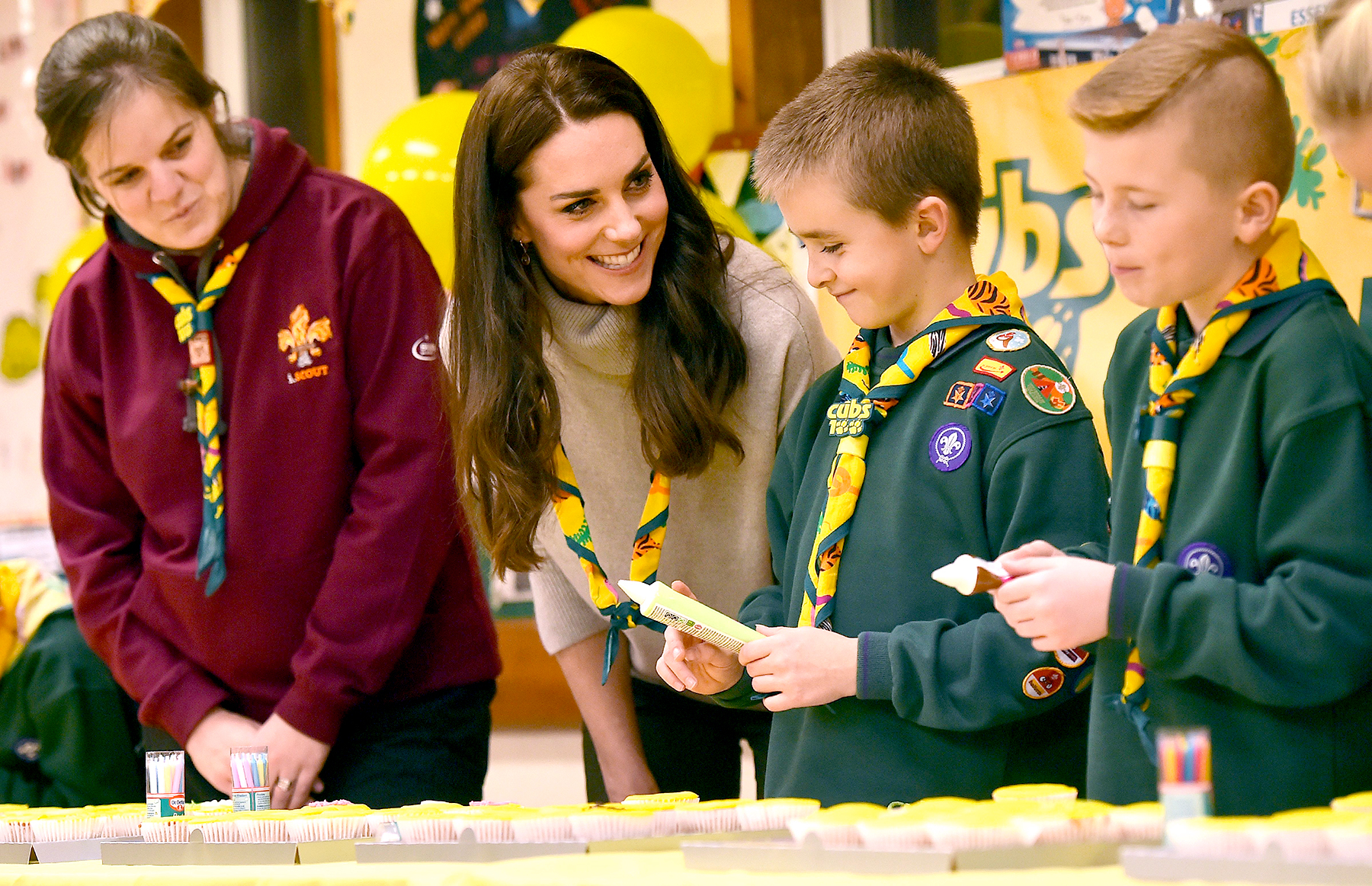 Britain's Catherine, Duchess of Cambridge (2L), ices cupcakes during a Cub Scout Pack meeting with cubs from the Kings Lynn District, in Kings Lynn, eastern England, on December 14, 2016, to celebrate 100 years of Cubs. The Duchess attended a special Cub Scout Pack meeting with Cubs from the Kings Lynn District to celebrate 100 years of Cubs. Cub Scouting was co-founded by Robert Baden-Powell and Vera Barclay on the 16th December 2016.