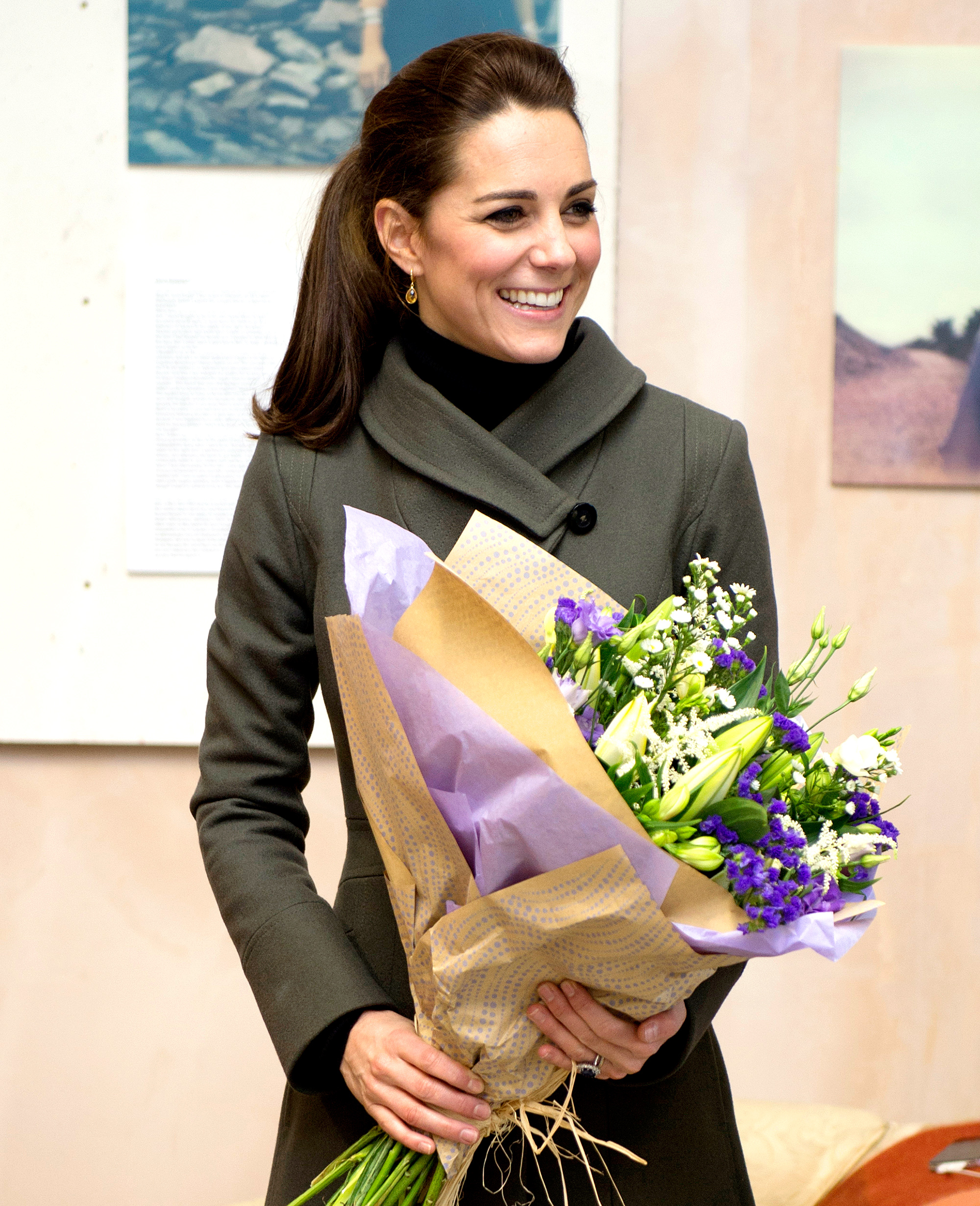 Kate Middleton receives a bouquet of flowers as she visits a photographic exhibition entitled
