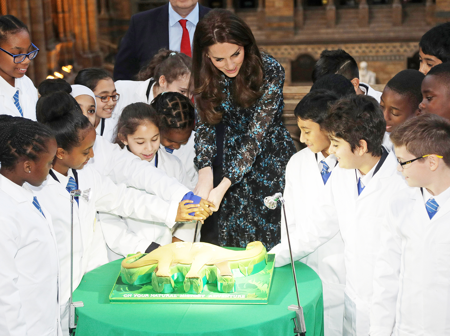 The Duchess of Cambridge cuts a cake with pupils from Oakington Manor Primary School in Wembley, as she attends a children's tea party at the Natural History Museum, London, to celebrate Dippy the Diplodocus's time in Hintze Hall.