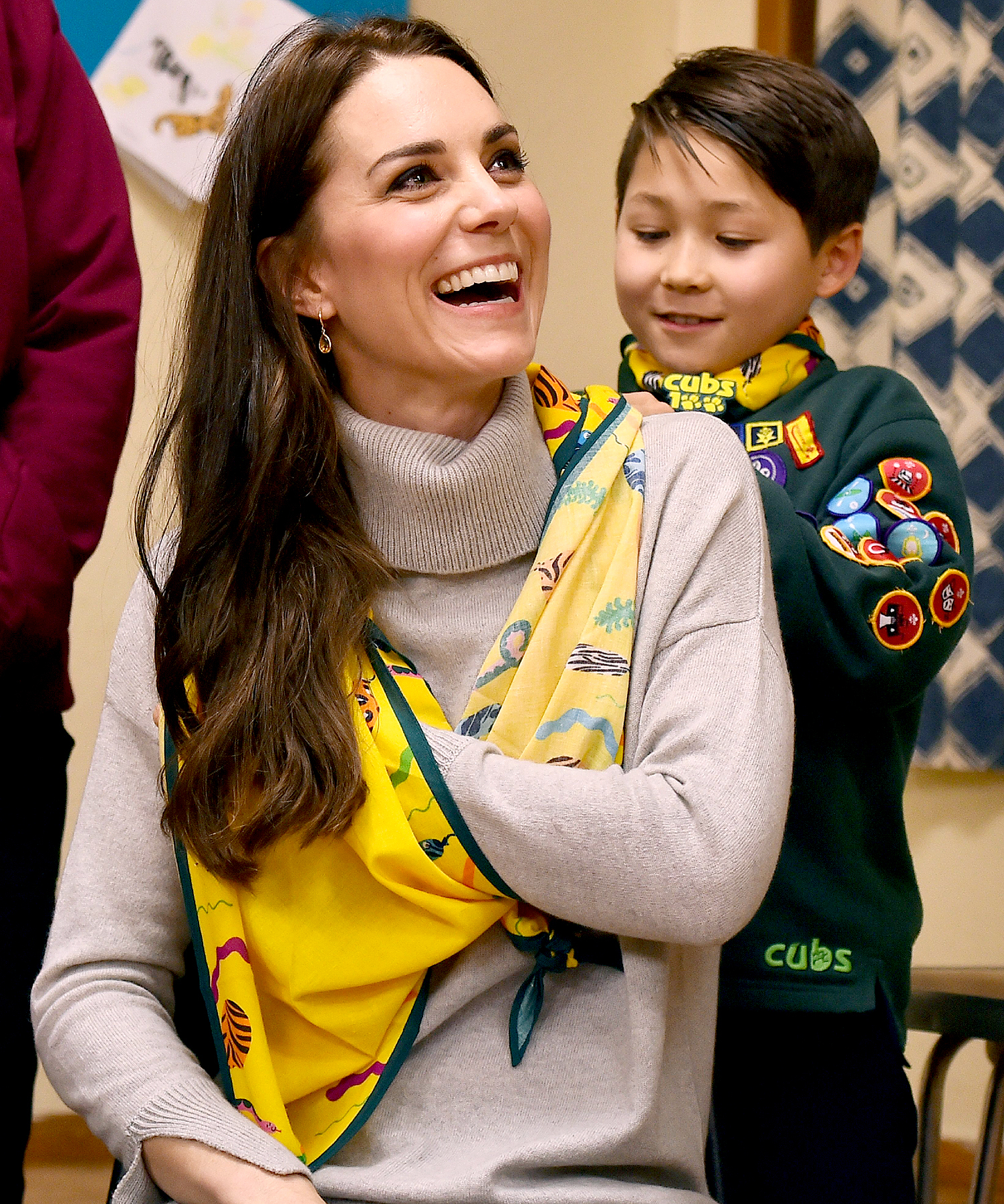 A cub scout uses a neckerchief to show Britain's Catherine, Duchess of Cambridge, how to support a broken arm, during a Cub Scout Pack meeting with cubs from the Kings Lynn District, in Kings Lynn, eastern England, on December 14, 2016, to celebrate 100 years of Cubs. The Duchess attended a special Cub Scout Pack meeting with Cubs from the Kings Lynn District to celebrate 100 years of Cubs. Cub Scouting was co-founded by Robert Baden-Powell and Vera Barclay on the 16th December 1916.