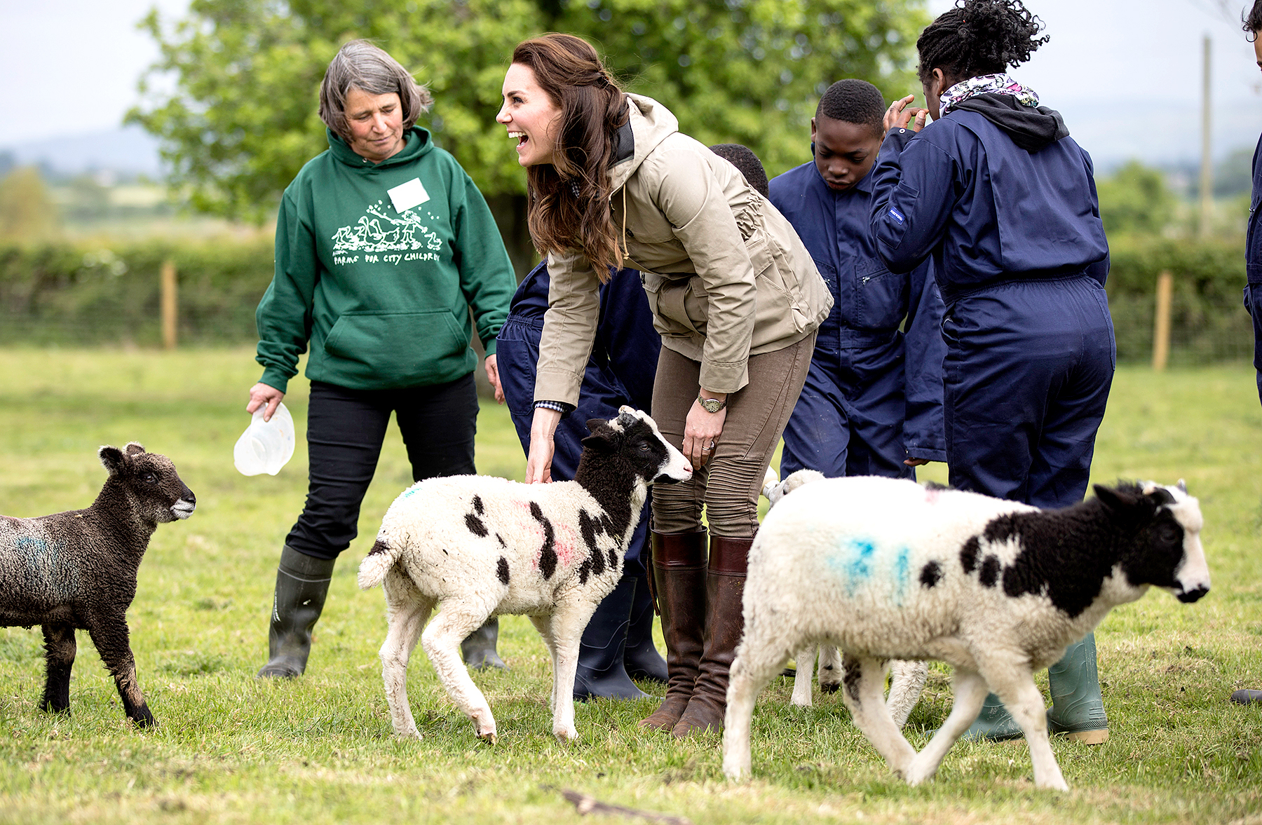 """The Duchess of Cambridge with the sheep and lambs and children from Vauxhall primary school in London during a visit to a """"Farms for Children"""" farm on May 3, 2017 in Arlingham, Gloucestershire."""