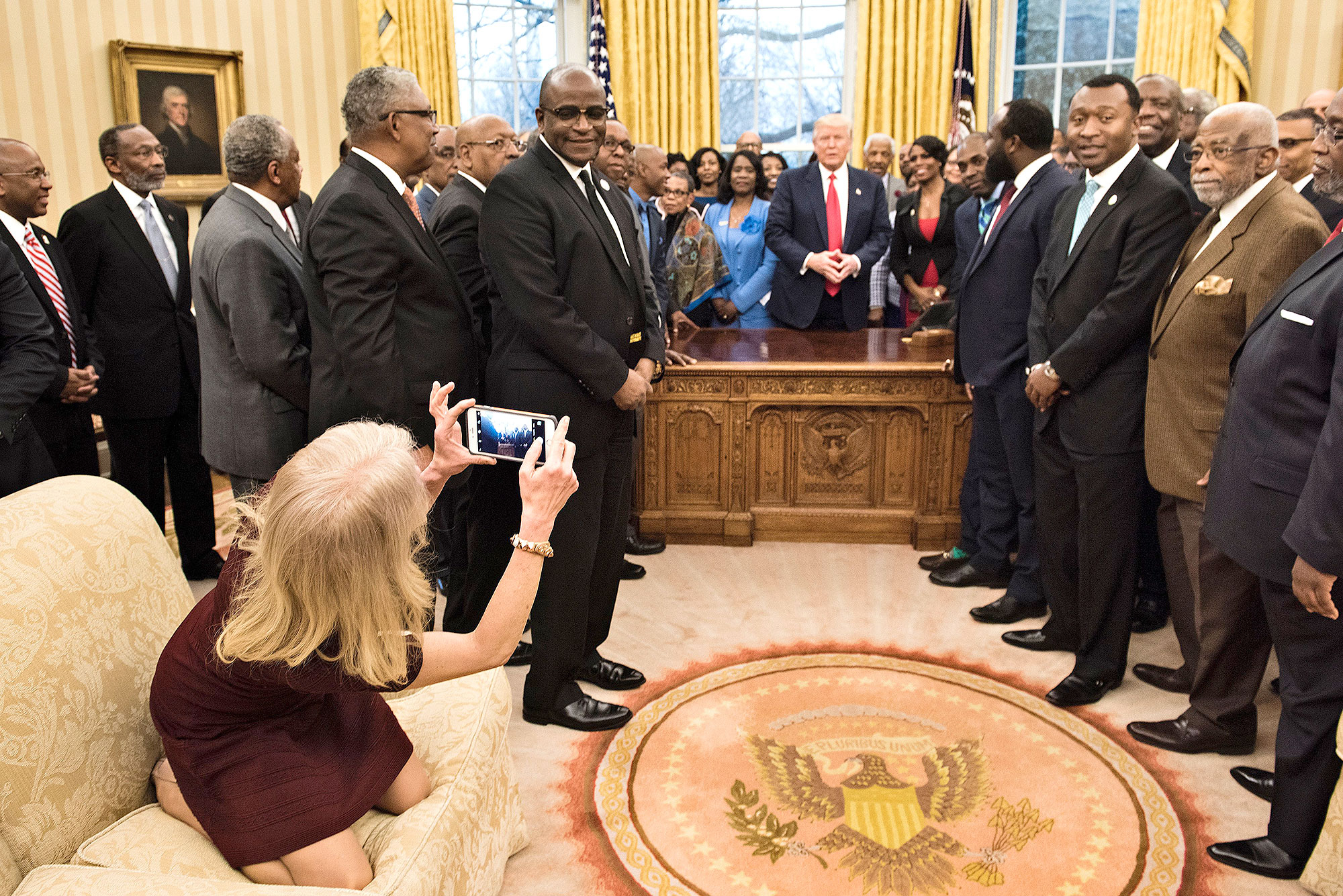 Counselor to the President Kellyanne Conway takes a photo as US President Donald Trump and leaders of historically black universities and colleges talk before a group photo in the Oval Office