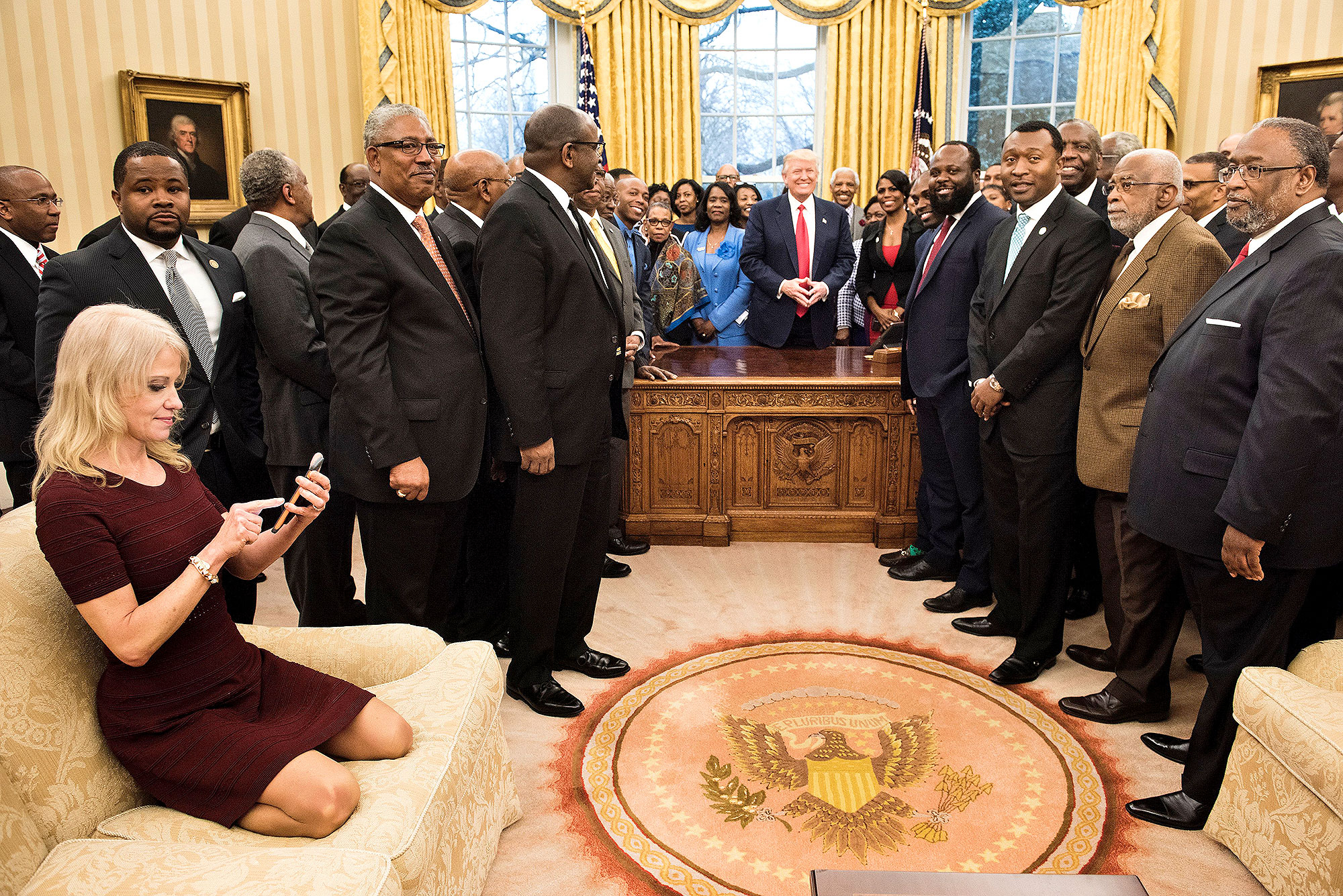 Counselor to the President Kellyanne Conway (L) checks her phone after taking a photo as US President Donald Trump and leaders of historically black universities and colleges pose for a group photo in the Oval Office of the White House before a meeting with US Vice President Mike Pence February 27, 2017 in Washington, DC.