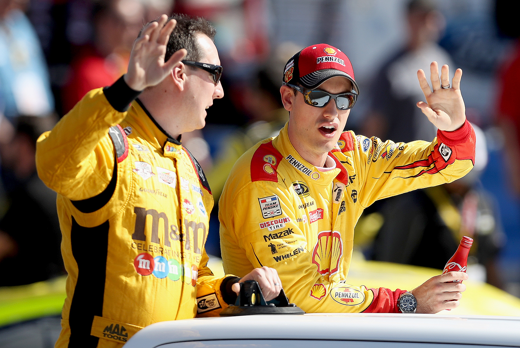 Kyle Busch, driver of the #18 M&M's Toyota, and Joey Logano, driver of the #22 Shell Pennzoil Ford, wave during driver introductions prior to the NASCAR Sprint Cup Series Can-Am 500 at Phoenix International Raceway on November 13, 2016 in Avondale, Arizona.