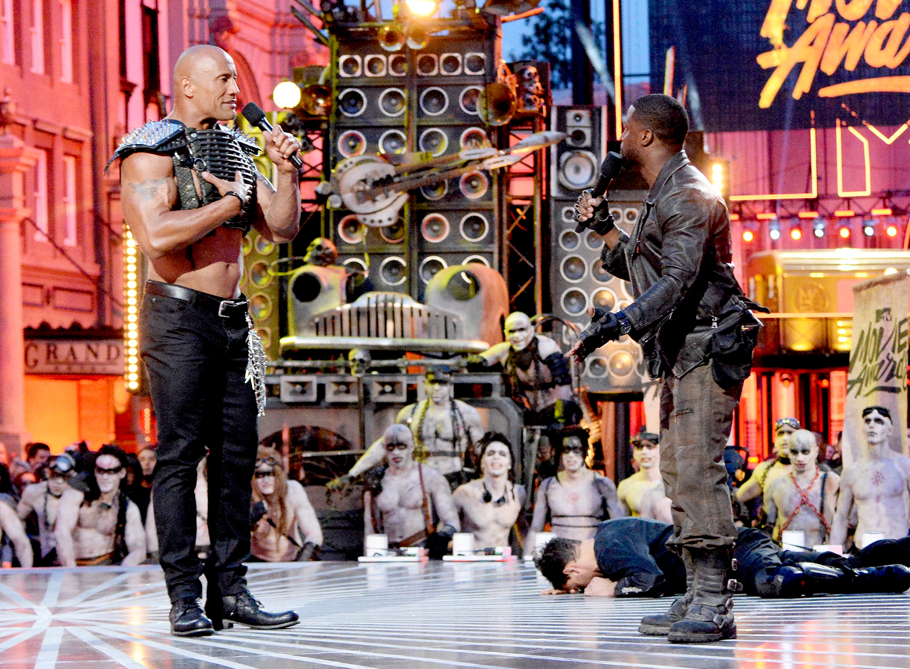 Dwayne Johnson and Kevin Hart speak onstage during the 2016 MTV Movie Awards.