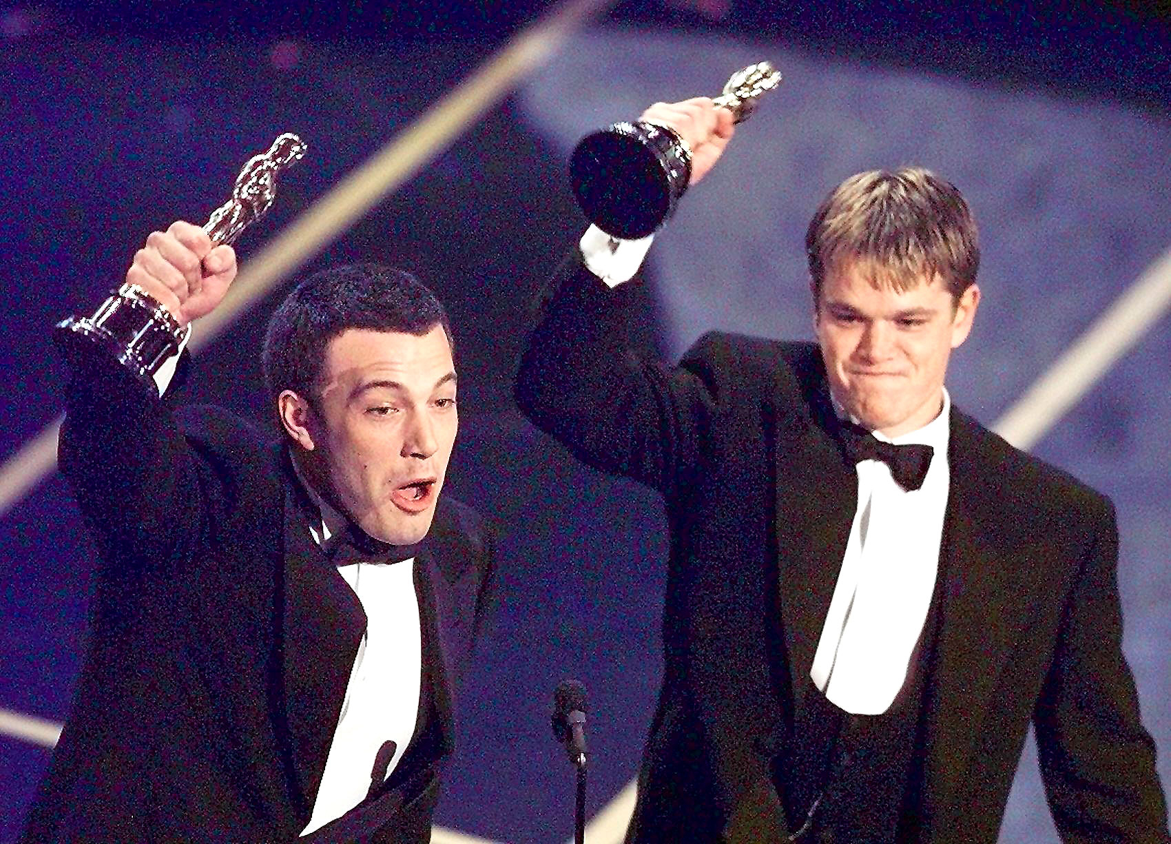 "Ben Affleck (L) and Matt Damon hold up their Oscars after winning in the Original Screenplay Category during the 70th Academy Awards at the Shrine Auditorium 23 March. The two won for their Original Screenplay ""Good Will Hunting."""