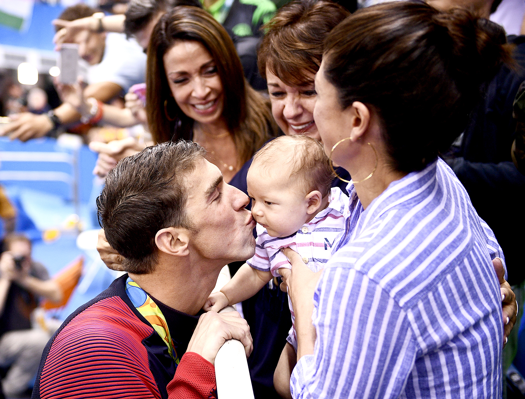 USA's Michael Phelps (L) kisses his son Boomer next to his partner Nicole Johnson (R) and mother Deborah (C) after he won the Men's 200m Butterfly Final during the swimming event at the Rio 2016 Olympic Games at the Olympic Aquatics Stadium in Rio de Janeiro on August 9, 2016.