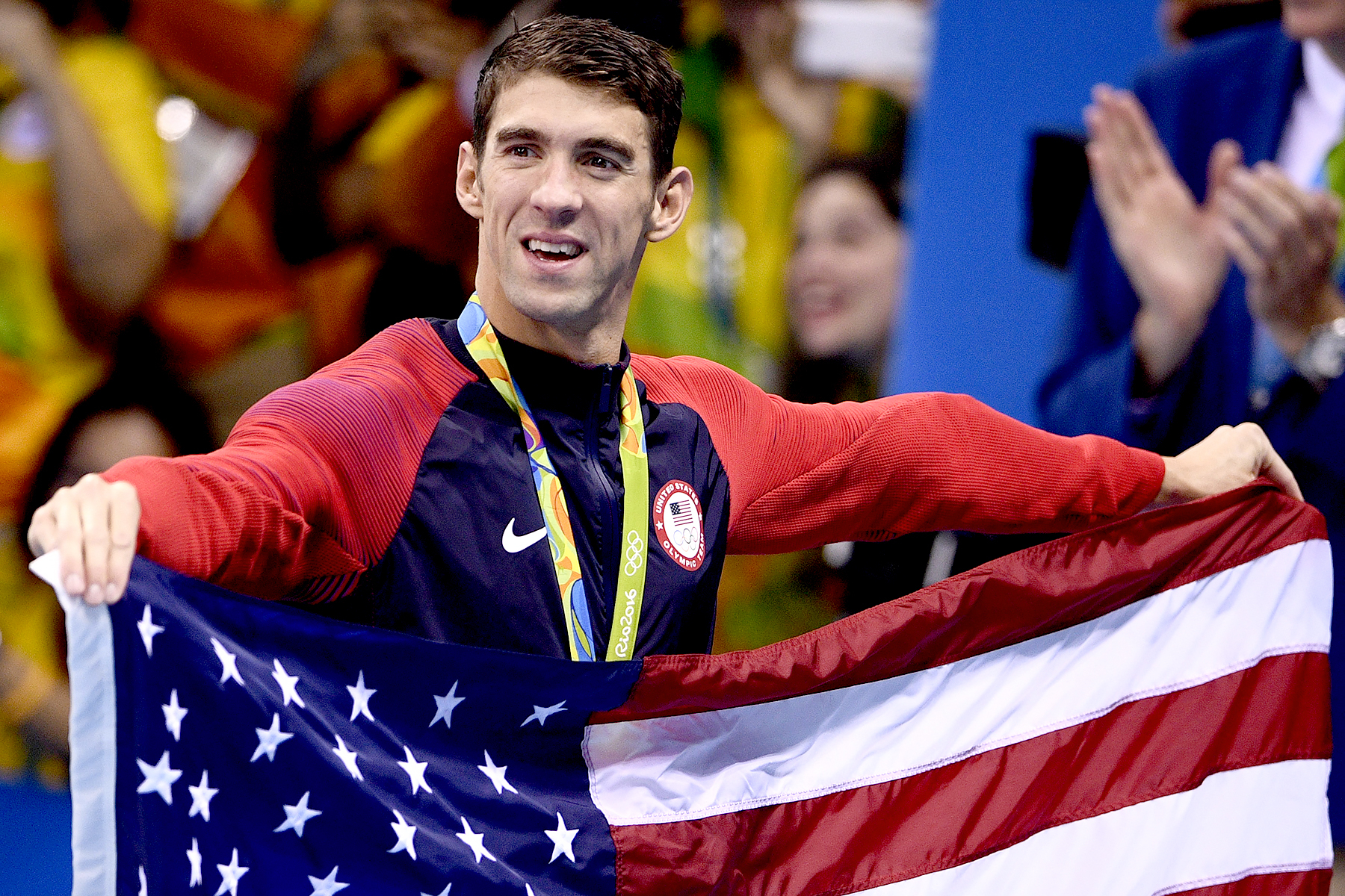 USA gold medalist Michael Phelps holds the U.S. flag after the podium ceremony of the men's swimming 4x100m Medley Relay Final at the Rio 2016 Olympic Games at the Olympic Aquatics Stadium in Rio de Janeiro on August 13, 2016.