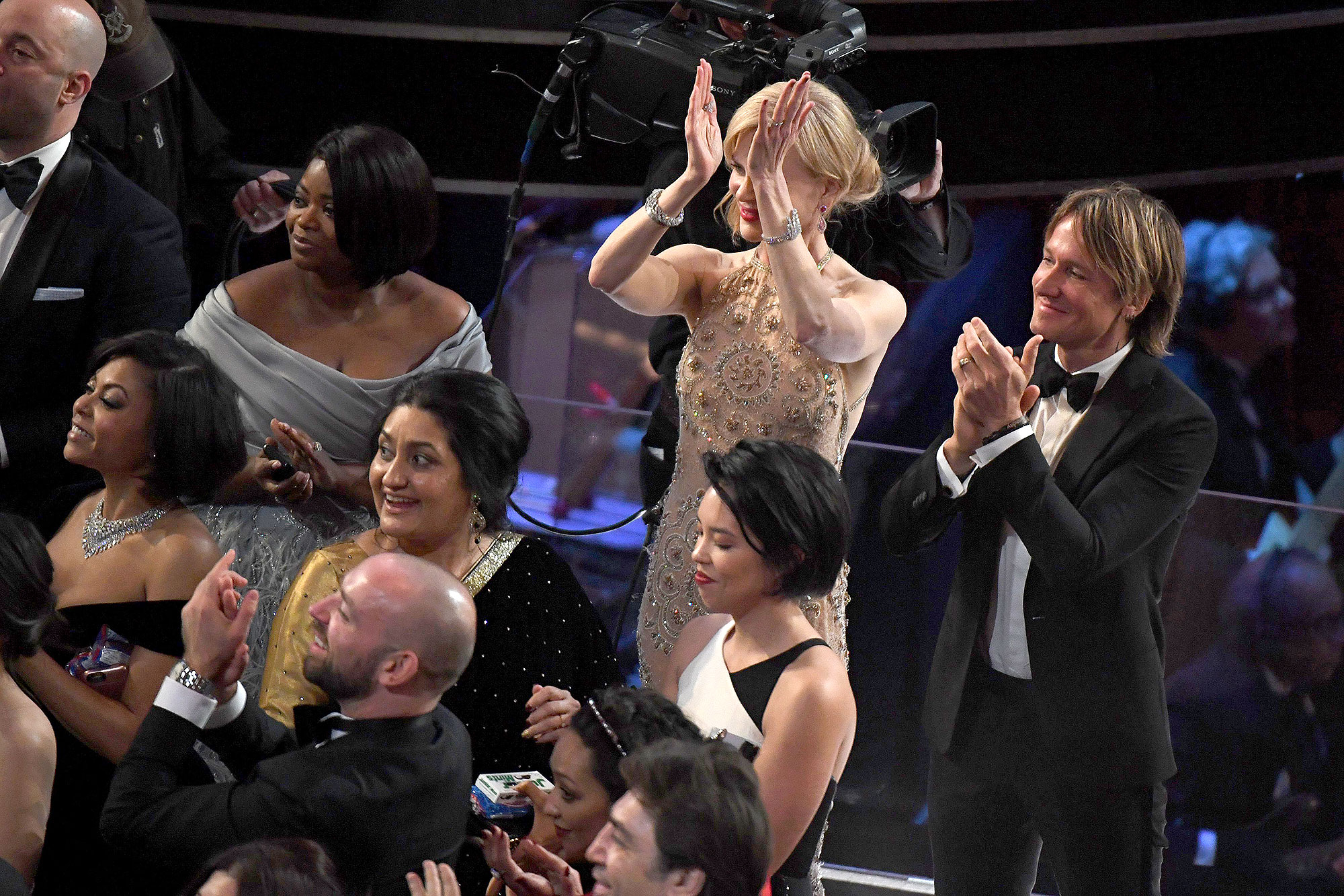 "Nominee for Best Supporting Actress in ""Lion"" Nicole Kidman (C), her husband Australian singer Keith Urban (R) and nominee for Best Supporting Actress in ""Hidden Figures"" Octavia Spencer applaud as tourists are brought into the Oscars as a surprise at the 89th Oscars on February 26, 2017 in Hollywood, California."