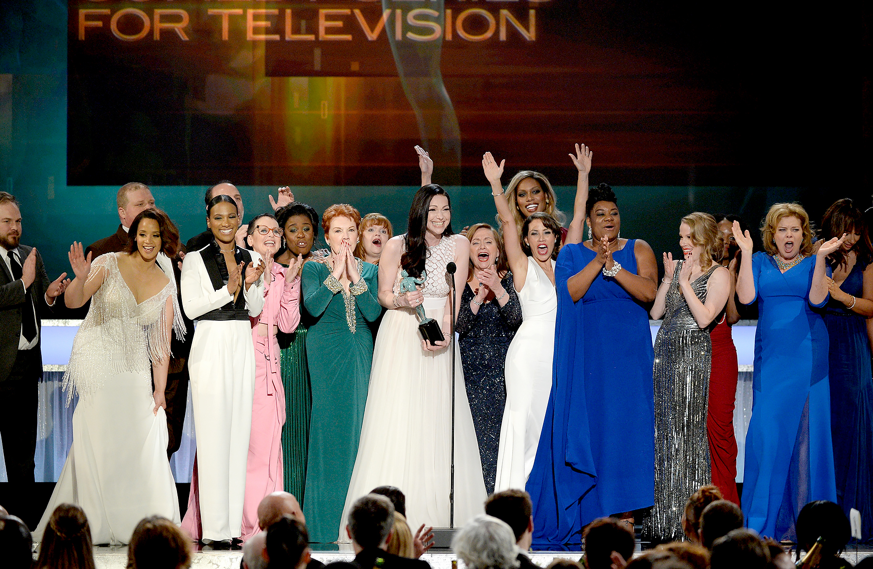 The cast of 'Orange Is the New Black,' including actors Vicky Jeudy, Lori Petty, Uzo Aduba, Kate Mulgrew, Annie Golden, Laura Prepon, Dale Soules, Laverne Cox, and Michelle Hurst, accept Outstanding Performance by an Ensemble in a Comedy Series award onstage during the 22nd Annual Screen Actors Guild Awards.