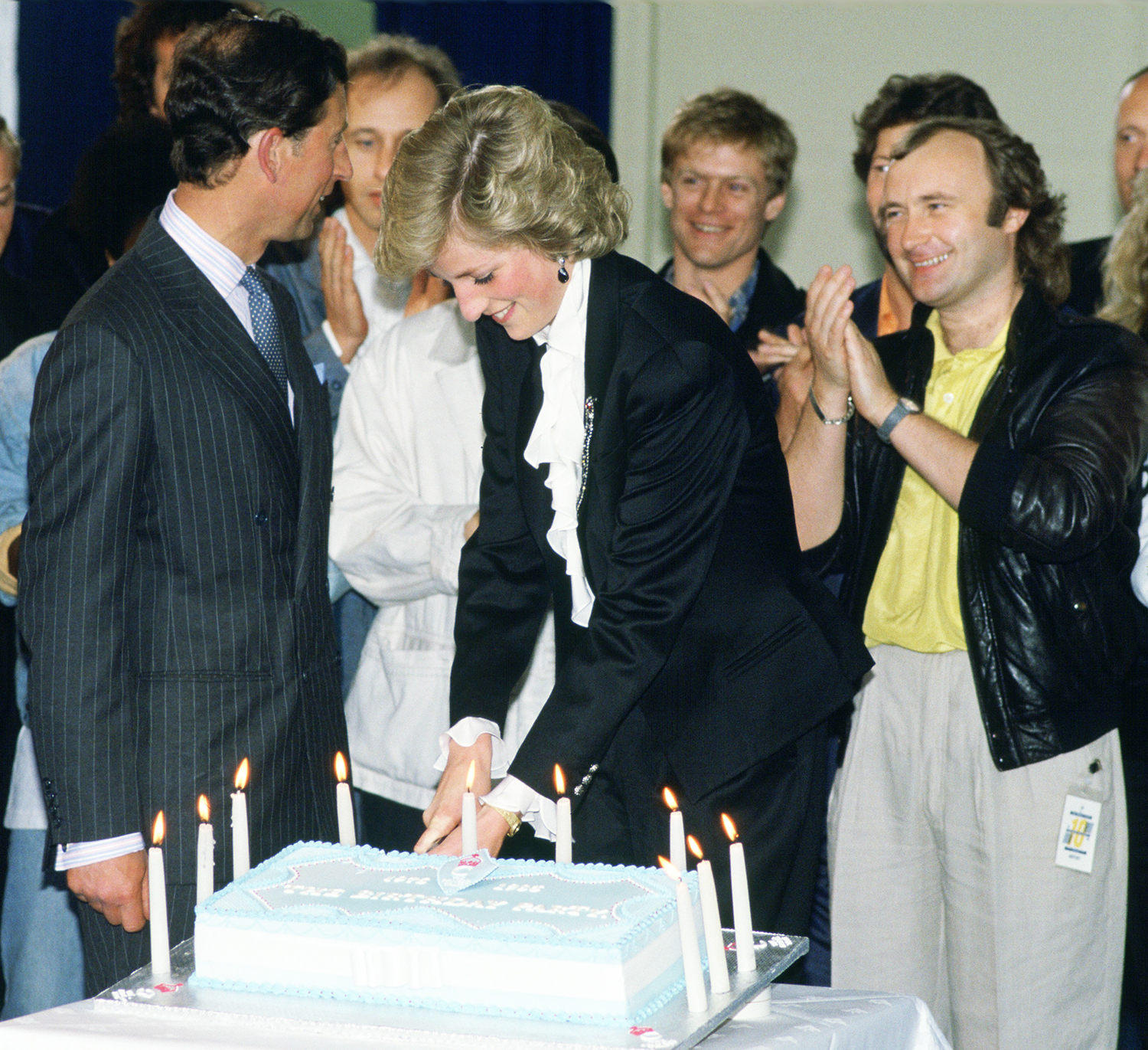 Diana, Princess of Wales and Prince Charles, Prince of Wales cutting a cake to celebrate ten years of the Prince's Trust Concert at Wembley, The singer and musician Phil Collins is standing on Diana's left