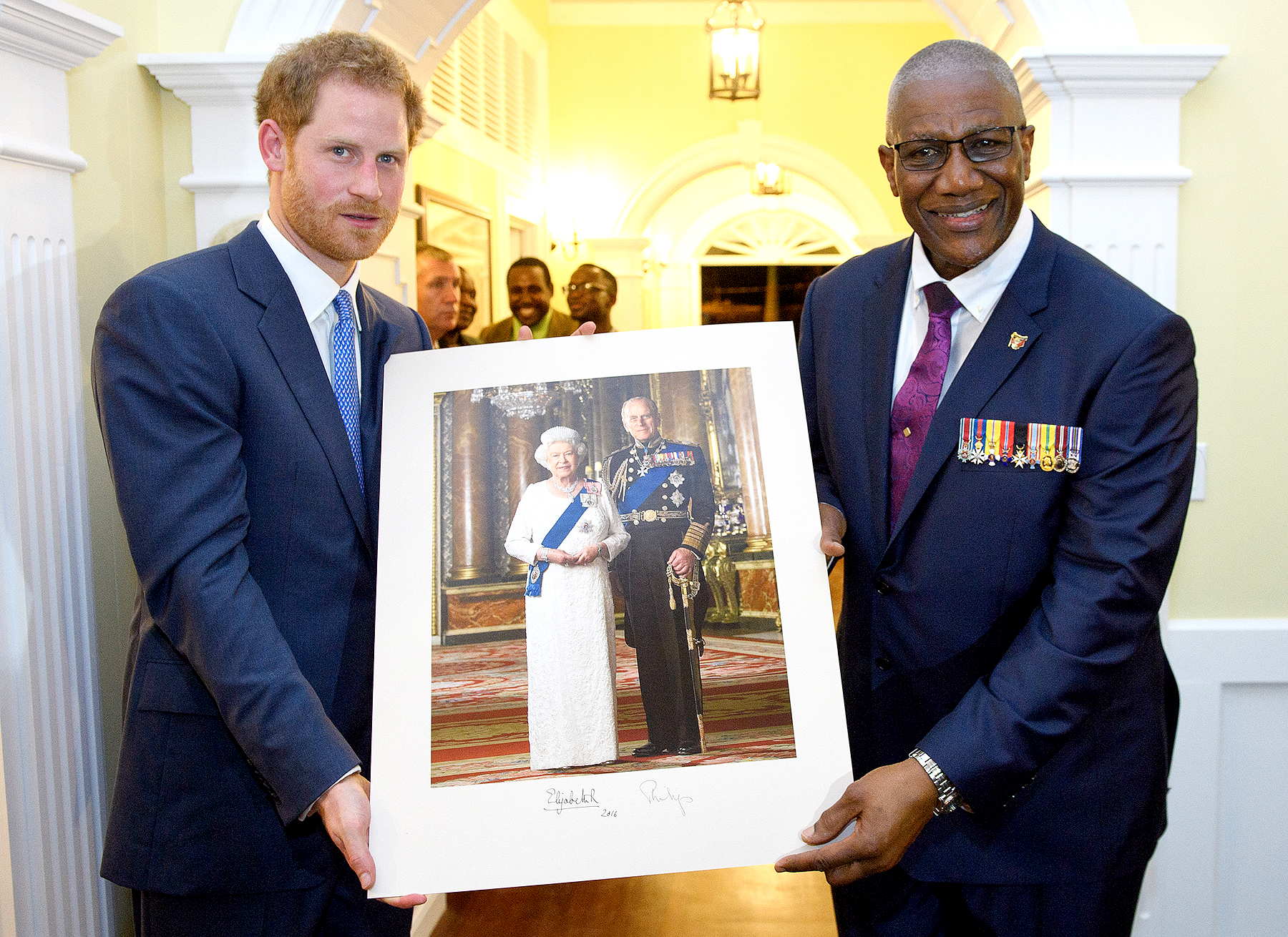 Prince Harry presents a photo of Queen Elizabeth II and Prince Philip, Duke of Edinburgh, as he attends a reception hosted by the Governor General, Sir Rodney Williams, at the newly renovated Clarence House on the first day of an official visit, on Nov. 20, 2016, in Antigua. Prince Harry's visit to the Caribbean marks the 35th anniversary of independence in Antigua and Barbuda and the 50th anniversary of independence in Barbados and Guyana.