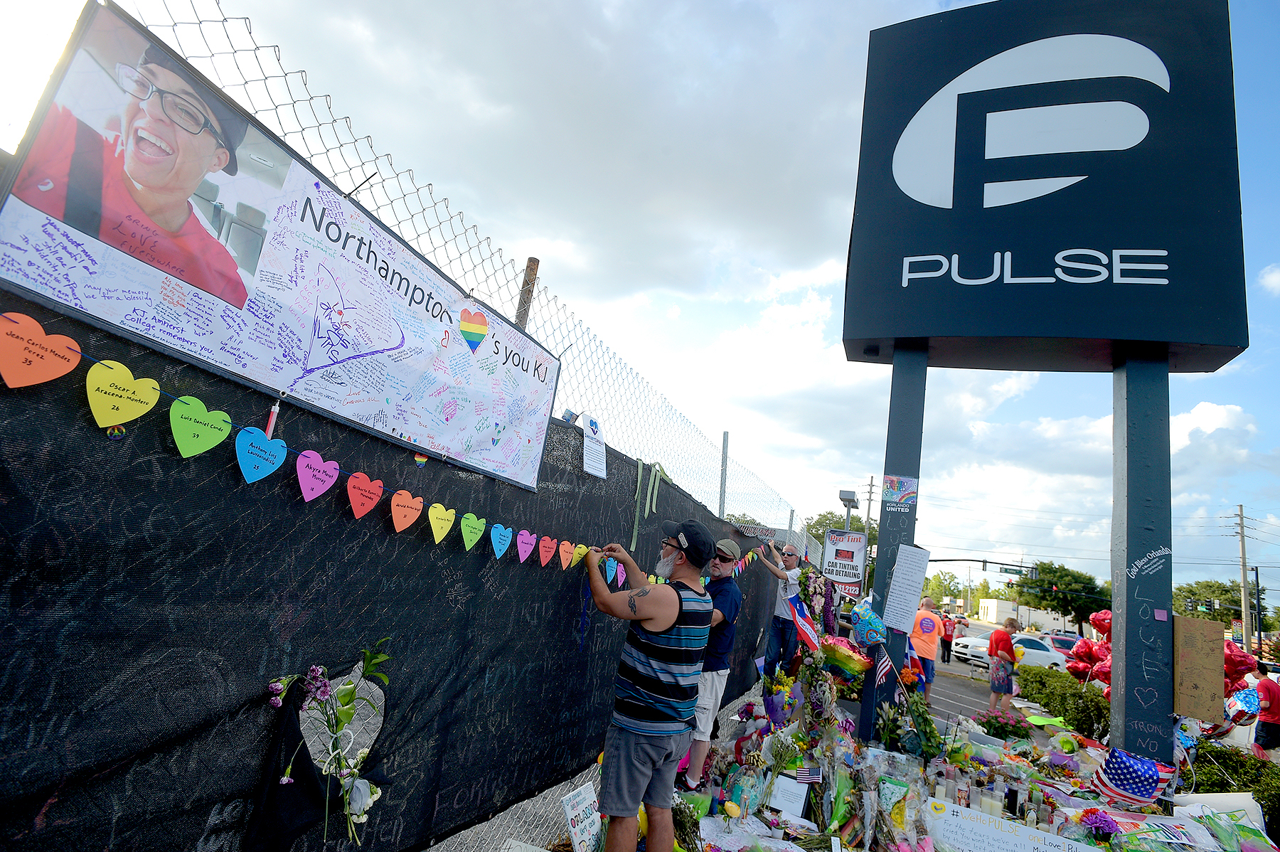 Mourners visit a makeshift memorial for victims of the Pulse nightclub shooting in front of the location, Saturday, June 25, 2016, in Orlando.