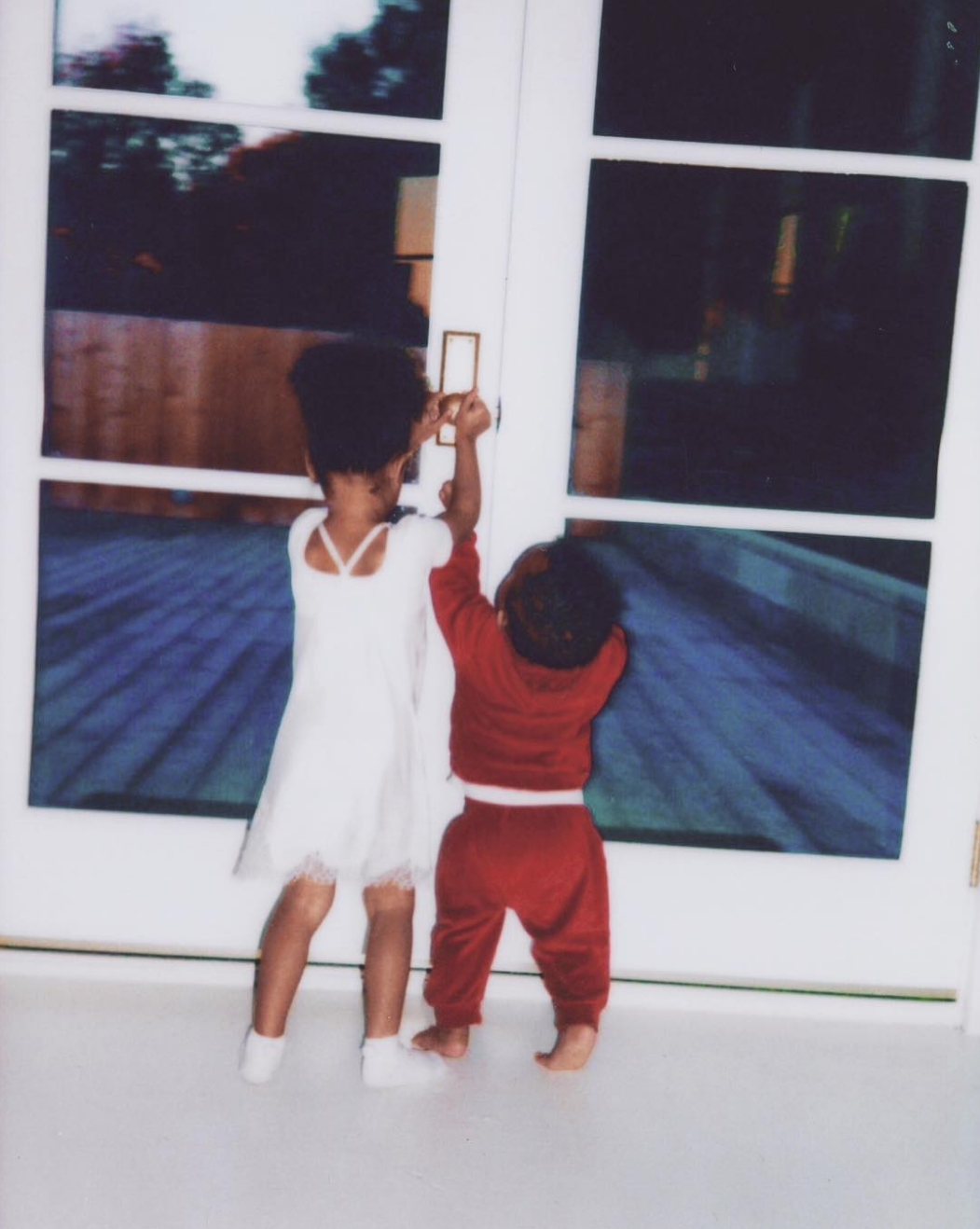 Kim Kardashian shared a pic of North helped her little brother Saint open a door in honor of National Siblings Day.