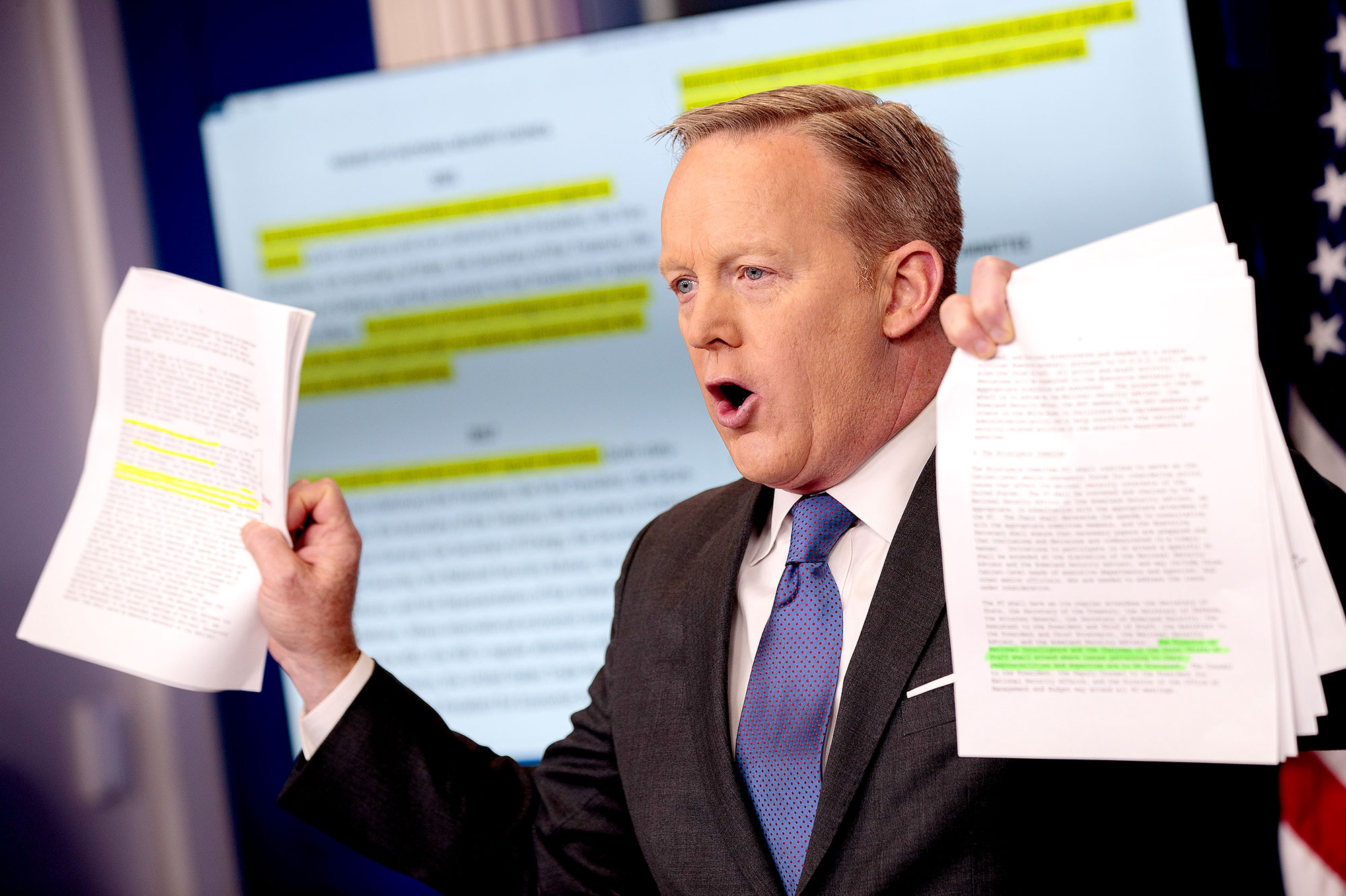 White House Press Secretary Sean Spicer holds up paperwork highlighting and comparing language about the National Security Council from the Trump administration and previous administrations during the daily press briefing at the White House, January 30, 2017 in Washington, DC.