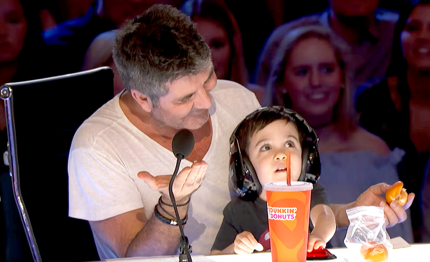 Eric Cowell sitting on the lap of his father Simon Cowell wearing a headset
