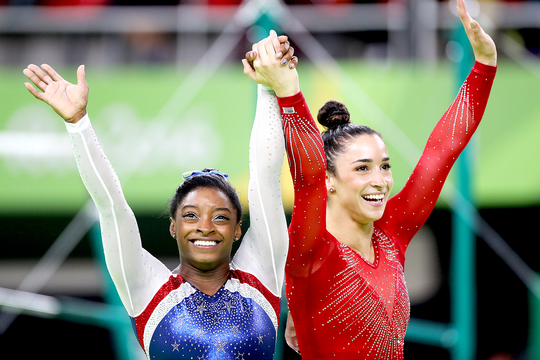 Simone Biles of the United State and Alexandra Raisman of the United States celebrate after winning Gold and Silver during the Artistic Gymnastics Women's Individual All-Around Final at the Rio Olympic Arena on August 11, 2016 in Rio de Janeiro, Brazil.