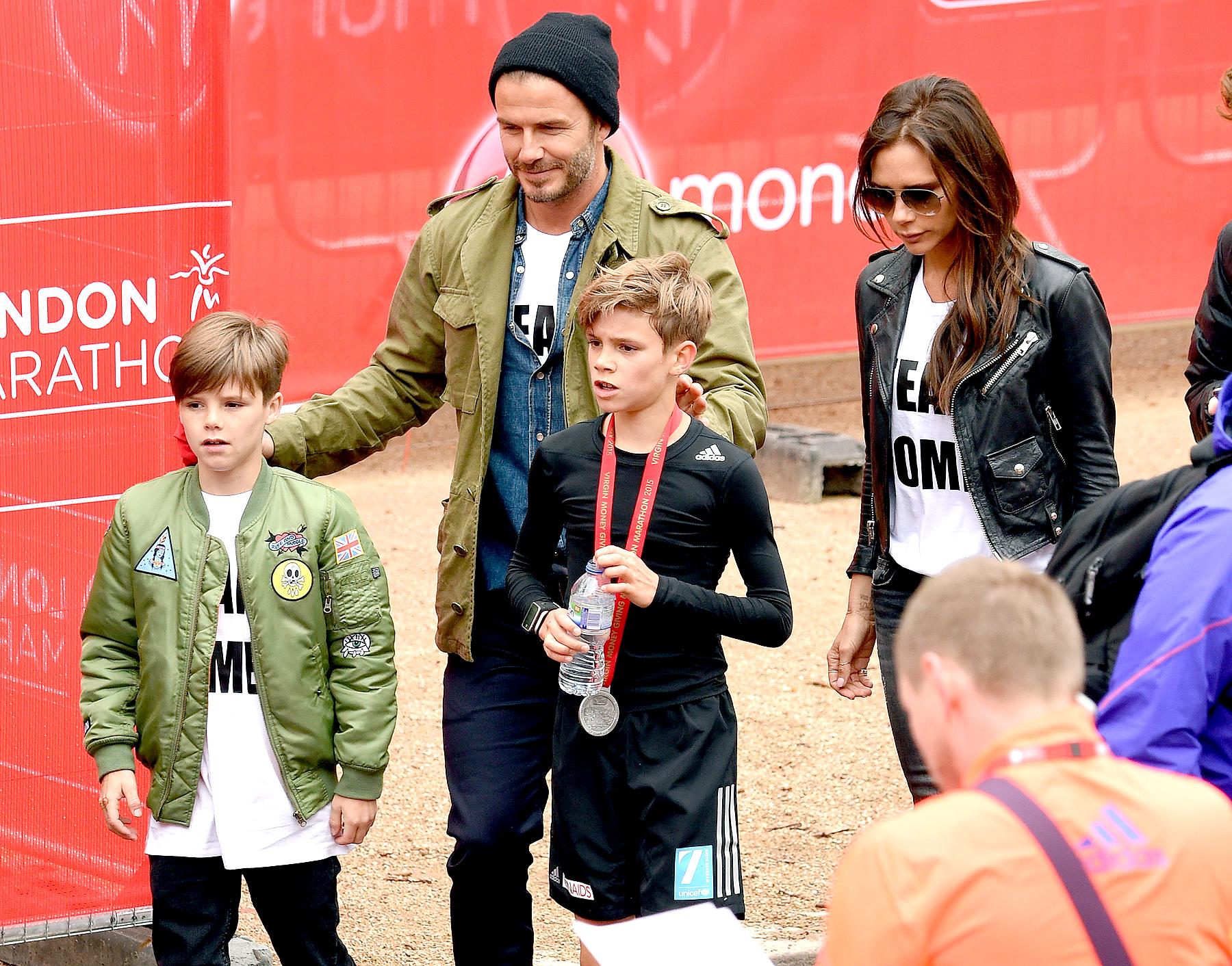 Cruz Beckham, David Beckham and Victoria Beckham congratulate Romeo Beckham after he finished the Childrns Marathon during the London Marathon on April 26, 2015 in London, England.
