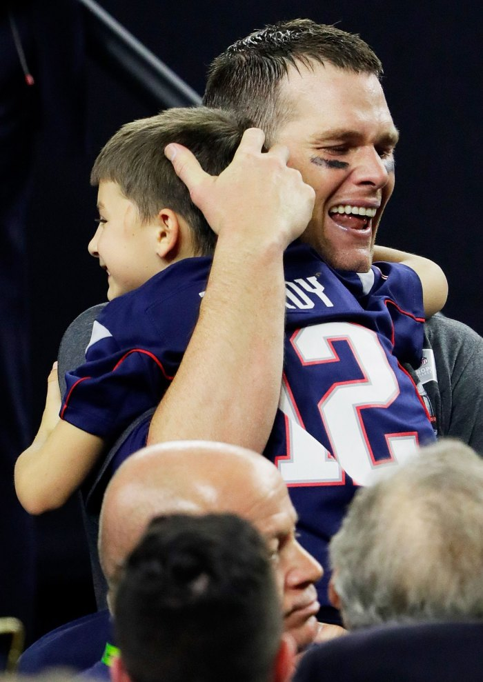 Tom Brady cries as he carries his son, Benjamin following the Super Bowl win