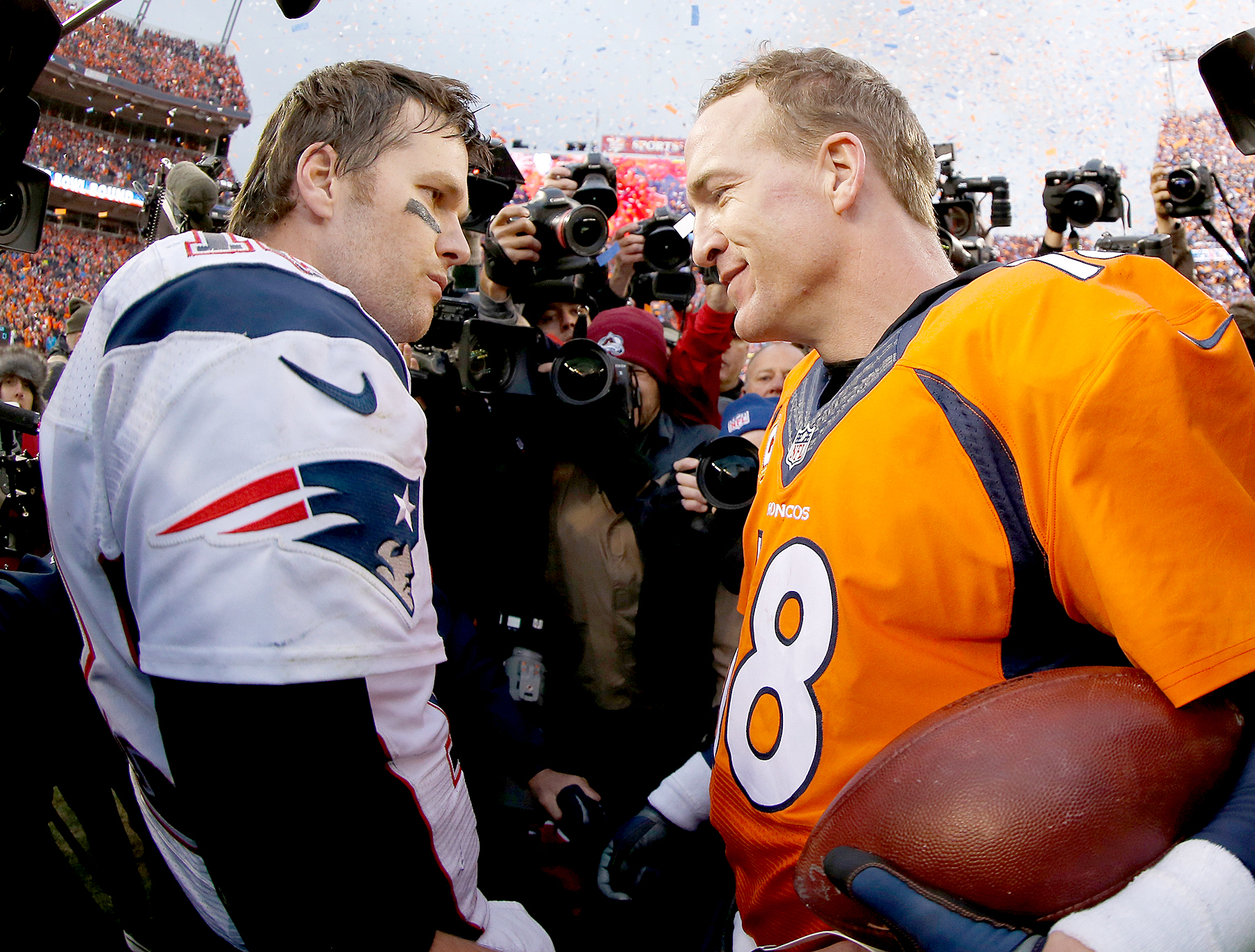 Peyton Manning, No. 18, of the Denver Broncos and Tom Brady, No. 12, of the New England Patriots speak after the AFC Championship game at Sports Authority Field at Mile High on January 24, 2016, in Denver.