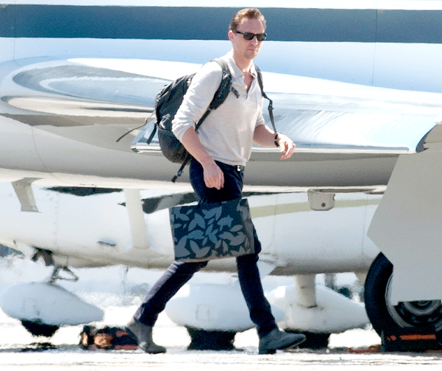 Tom Hiddleston is spotted boarding a private airplane in Los Angeles.