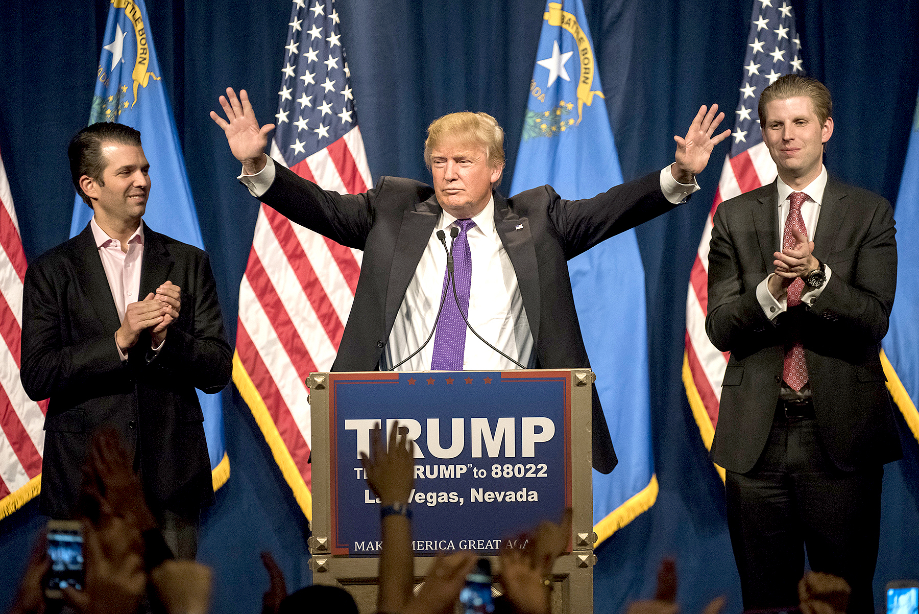 Donald Trump, center, gestures as his sons Donald Trump Jr., left, and Eric Trump, right, applaud during a caucus night rally in Las Vegas on Tuesday, Feb. 23, 2016.