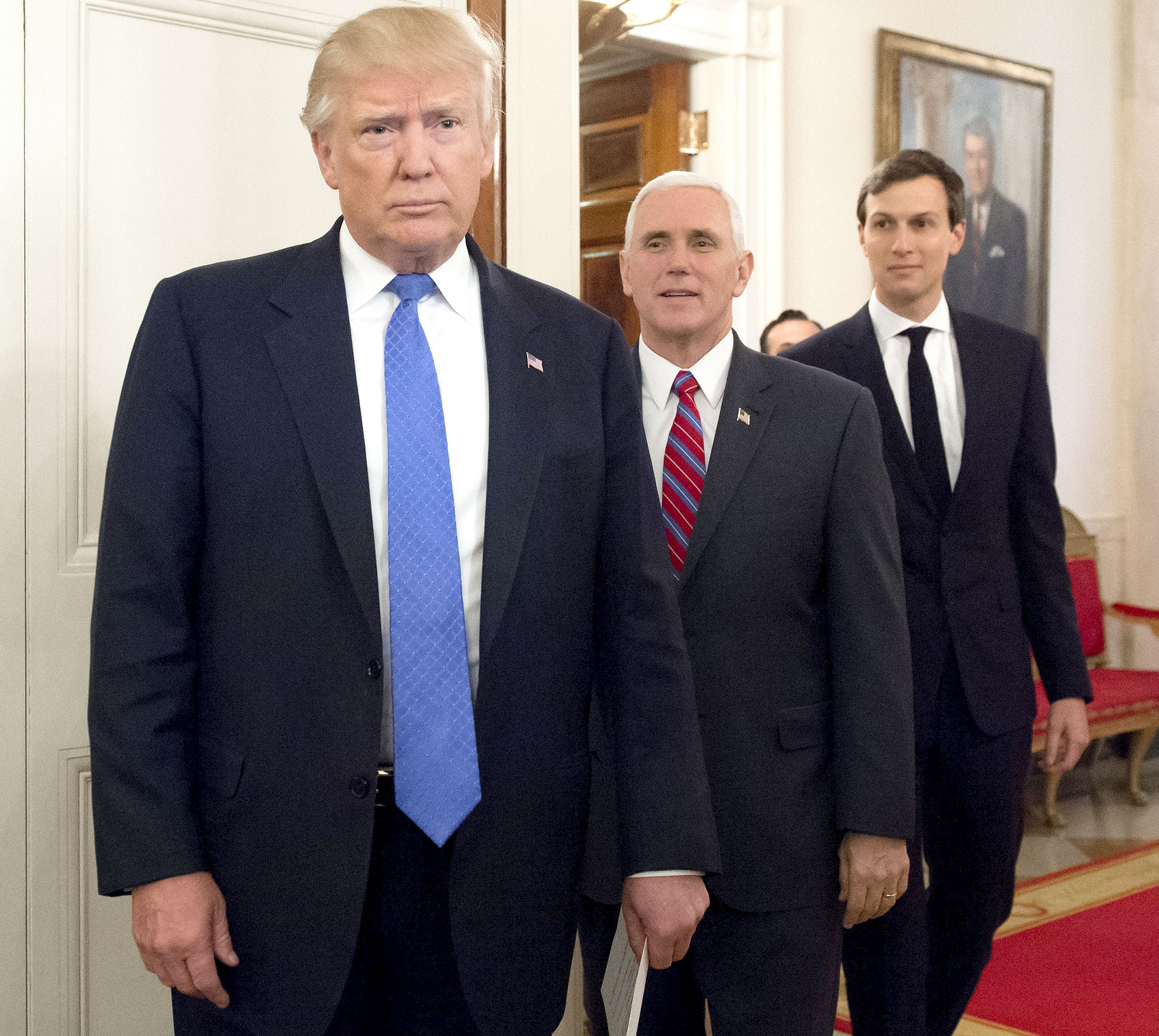 US President Donald Trump arrives alongside Vice President Mike Pence (C) and White House Senior Advisor Jared Kushner (R) during a meeting with manufacturing CEOs in the State Dining Room at the White House in Washington, DC, February 23, 2017.