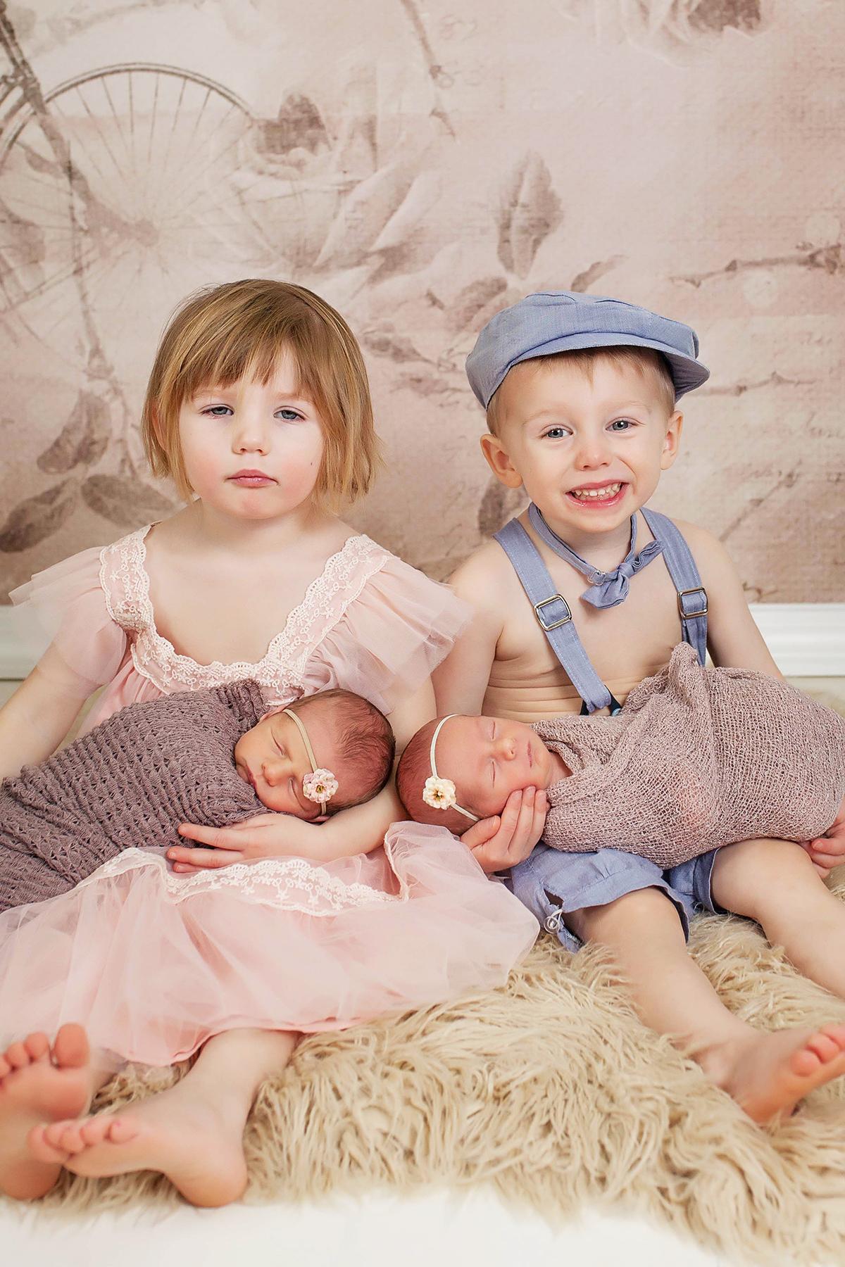 Toddler Twins Cuddling Their Newborn Twin Siblings bored