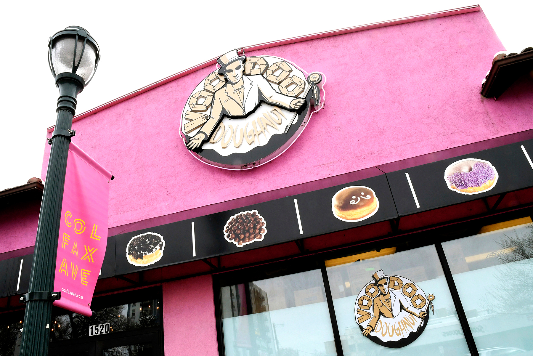 The company sign hangs over the windows of the storefront of Voodoo Doughnuts on East Colfax Avenue in Denver on Tuesday, April 4, 2017.