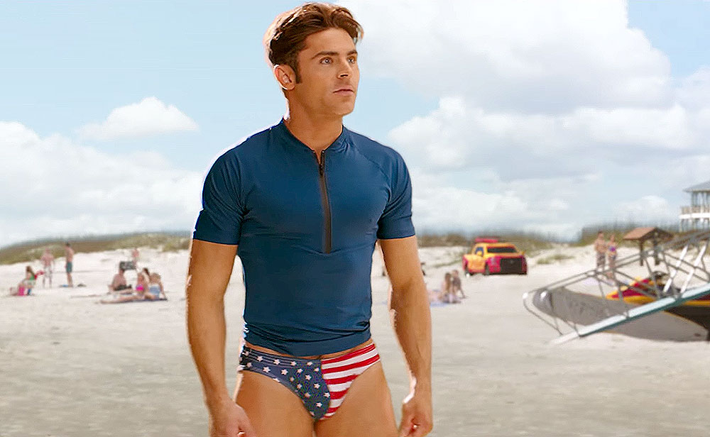 31537e45e As Johnson, 44, rips off his sweatpants to reveal a pair of red board  shorts, the High School Musical alum strips down to his star-spangled  swimwear.